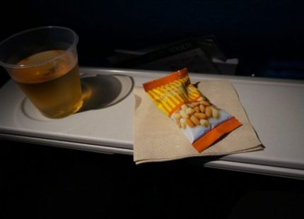Airplane tray table with a full plastic cup and a bag of peanuts on a napkin.